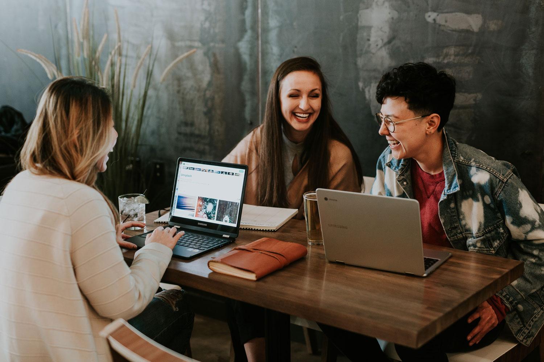 Bild zeigt drei Frauen mit Laptops beim Meeting im Café